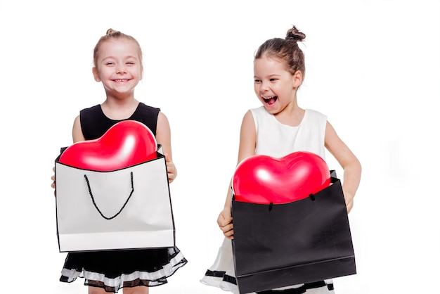 Photo of 2 little girls with elegant dresses hold large bags with heart-shaped balloons inside