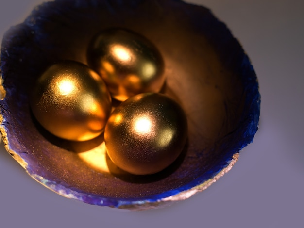 Photo of 3 easter eggs painted with bright gold paint lying on a decorative handmade plate painted