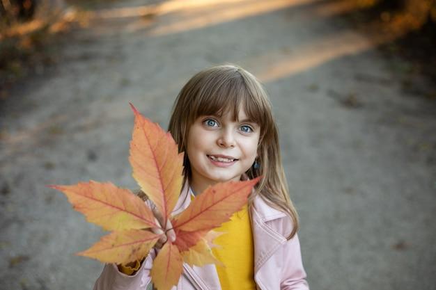 Фото красивая девочка в осеннем парке с желтым листом каштана