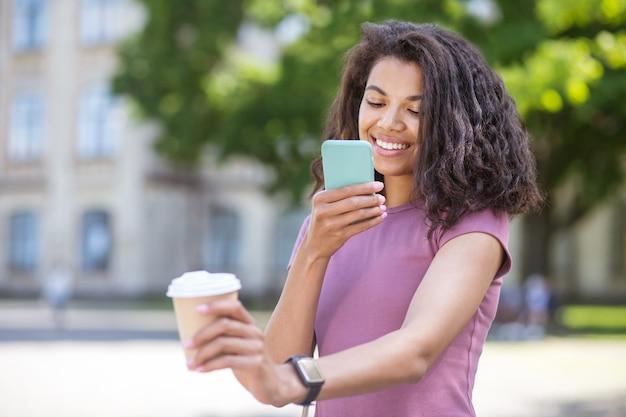 Фото. девушка фотографирует чашку с кофе на смартфоне Premium Фотографии