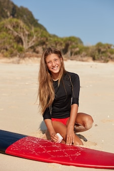 Photo of active female surfer dressed in swimsuit, has long hair, pleasant smile on face, prepares her surfboard by waxing surface before session