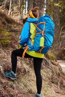 Photo of active female tourist climbs on hill of mountains, carries big rucksack, wears boots