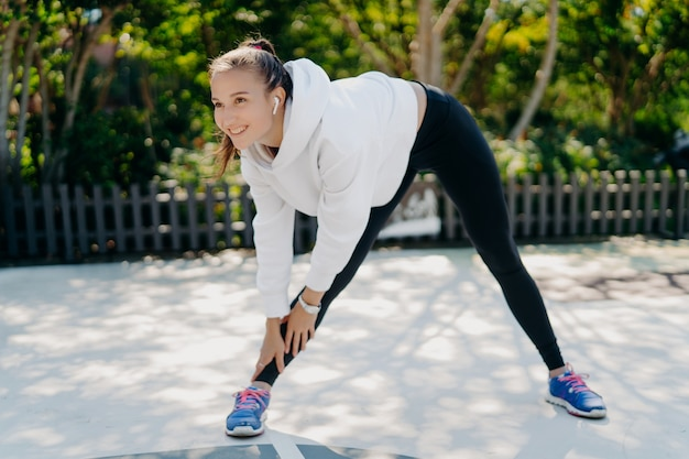 Photo of active pleased woman smiles gladfully concentrated into distance leans to leg dressed in sportswear trains outdoors being motivated listens music in wireless earphones does aerobic exercises