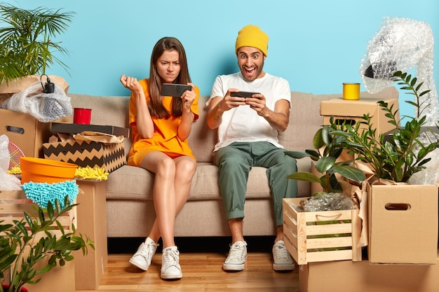 Photo of addicted millennial guy and girl play online games on smartphones