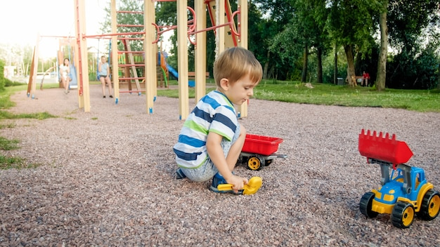 Photo of adorable 3 years old toddler boy playing with sand and you truck and trailer in park