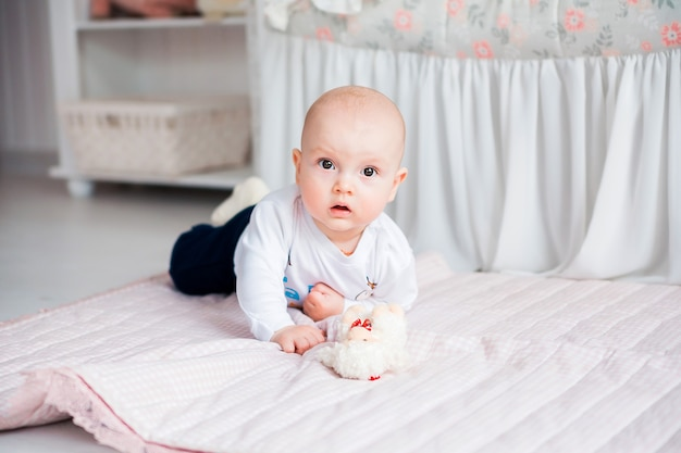 Photo of adorable baby boy laying on the floor in her nursery and play with toy