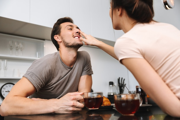 Photo of adorable couple man and woman sitting at table in flat, and having breakfast together