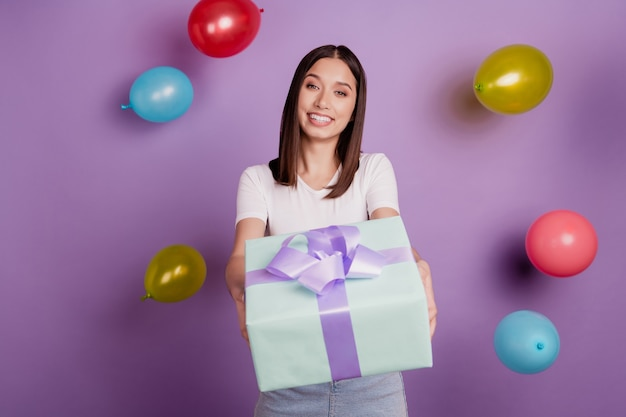 Photo of adorable lovely cheerful nice lady hold give present box balloons fall on purple background