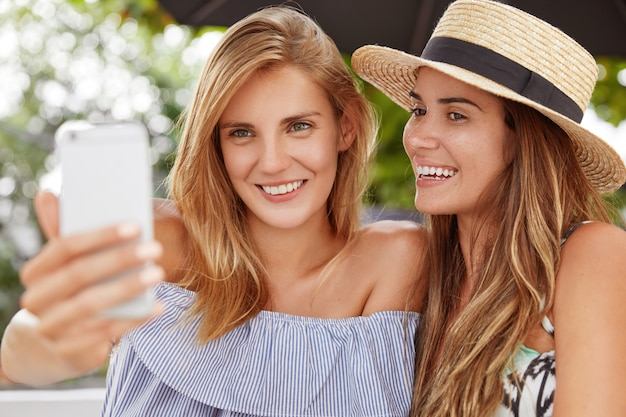 Photo of adorable young woman with light hair spends free time in company of her best friend, holds smart phone for making selfie, pose together in outdoor cafeteria, have positive expressions
