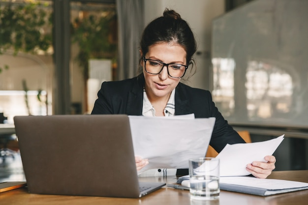 Photo of adult businesswoman 30s wearing formal clothing and eyeglasses working in office on laptop and examining paper documents, while holding in hand