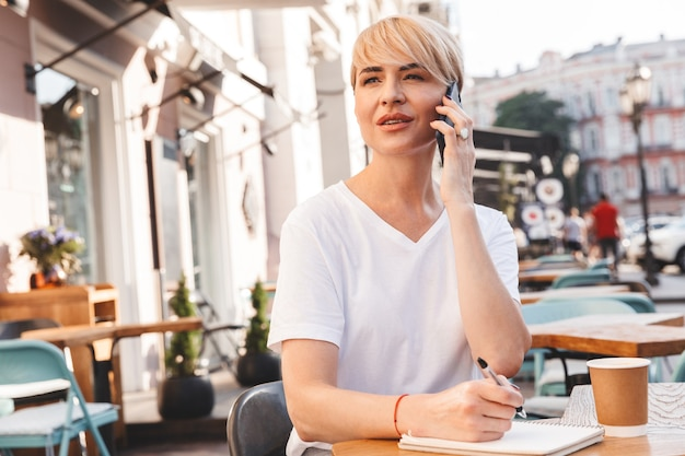 Photo of adult businesswoman wearing casual clothing sitting in summer cafe outdoor, while writing down in notebook and speaking on mobile phone