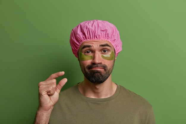 Photo of adult man with hydrogel patches under eyes for reducing puffines, wears waterproof shower cap, makes small gesture, tells he needs not much time for beauty treatments and date preparation