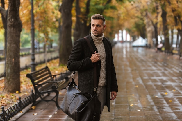 Photo of adult stylish man 30s wearing warm clothes walking outdoor through autumn park, and looking aside