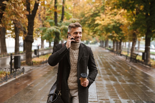 Photo of adult stylish man 30s wearing warm clothes walking outdoor through autumn park, and using mobile phone