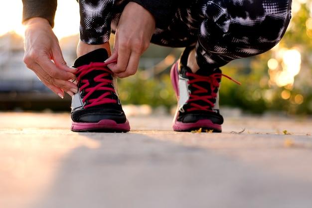 사진은 그녀의 신발 끈을 묶는 운동 여자