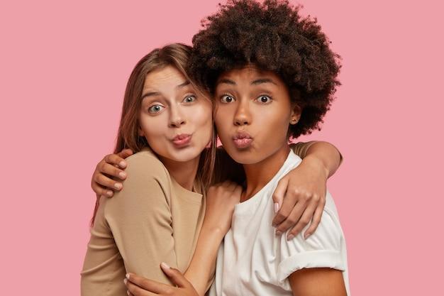 Foto di donne affettuose e adorabili di razza mista stanno vicine l'una all'altra, fanno una smorfia bacio