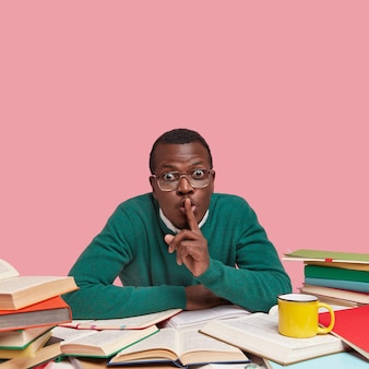 Photo of african american male bachelor keeps fore finger on lips, asks not making noise while studying, wears green sweater