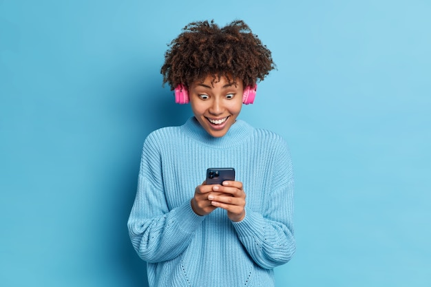 Photo of african american teenage girl stares impressed at smartphone display reads amazing news wears pink stereo headphones listens music dressed in knitted sweater