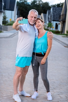 Photo after running. modern couple of mature businessmen feeling simply amazing while making selfie after running together
