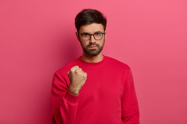 Photo of aggressive confident adult man has dark hair and beard, clenches fist and looks seriously , doesnt afford being insulted, shows his power, wears spectacles and red sweater.