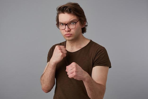 La foto di un ragazzo giovane aggressivo con gli occhiali indossa una maglietta vuota in piedi in posizione difensiva, tenendo i pugni chiusi, pronti a dare un pugno, si erge su sfondo grigio.