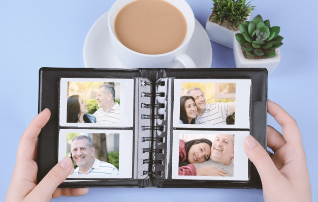 Photo album with instant photos of middle age couple