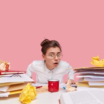 La foto di una giovane donna attraente stupita sembra stupita, indossa occhiali trasparenti, camicia bianca, lavora con i documenti