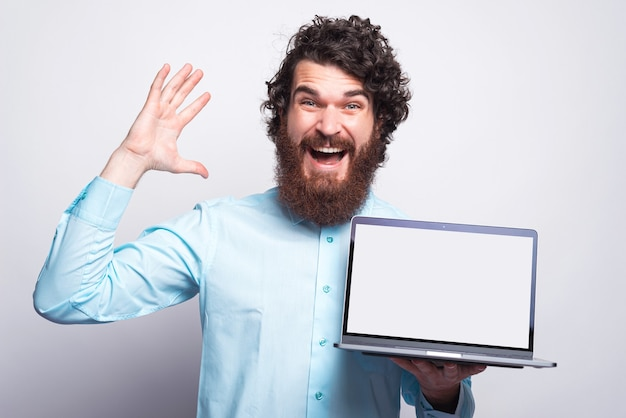 Photo of amazed bearded man in casual holding laptop with white empty screen