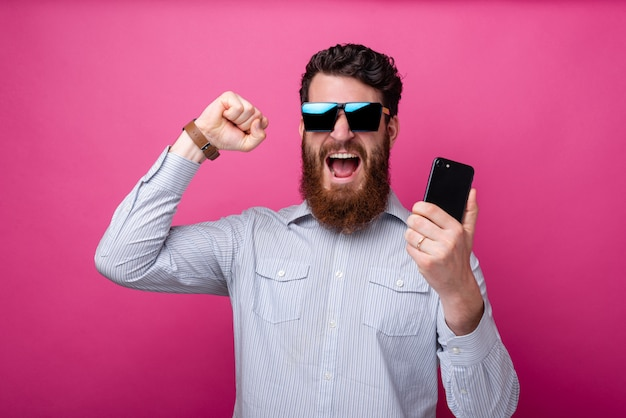 Photo of amazed bearded man in casual holding smartphone and celebrating victory