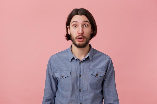 Foto di stupito barbuto giovane uomo con lunghi capelli scuri pettinati in camicia di jeans, isolato su sfondo rosa.