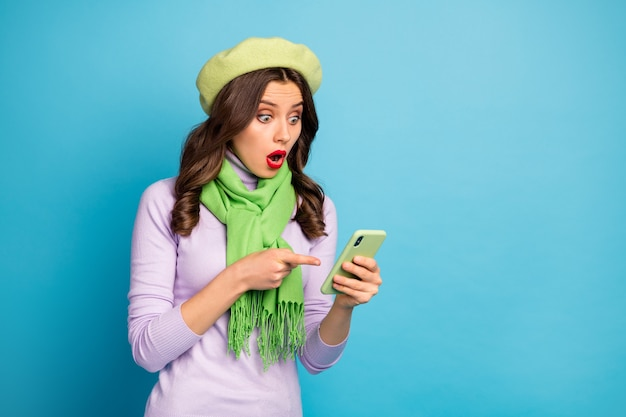 Photo of amazed crazy lady hold telephone read new post comments directing finger device screen wear green beret purple turtleneck scarf pants isolated blue color wall