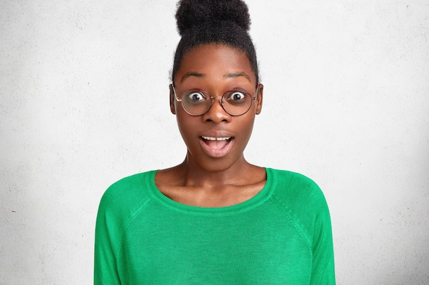 Photo of amazed dark skinned female looks with bated breath and unexpected expression, wears casual green sweater and round glasses