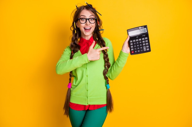 Photo of amazed girl messy hairdo point finger calculator wear shirt trousers isolated yellow color background