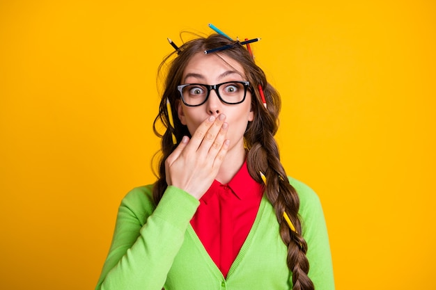 Photo of amazed girl with pencil hairdo cover lips hand wear geek clothes isolated yellow color background