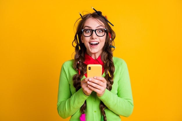 Photo of amazed girl with pencil hairdo hold cellphone wear shirt isolated on yellow color background