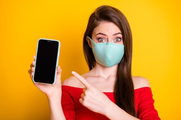写真驚いたヒップセットの女の子ショー新しいデビススマートフォンポイント人差し指は、covidプロモーションウェアレッドスタイルスタイリッシュなトレンディなトップ呼吸マスク分離された明るい輝きの色の背景を示しています