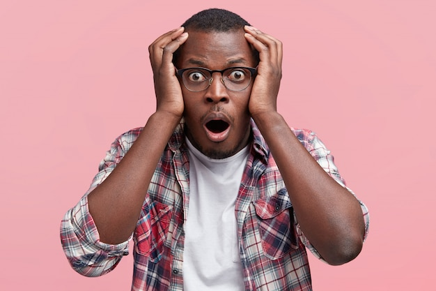 Photo of amazed shocked african american male looks in terror and with eyes popped out, keeps hands on head, keeps mouth widely opened, expresses unexpectedness and surprisment, isolated on pink wall