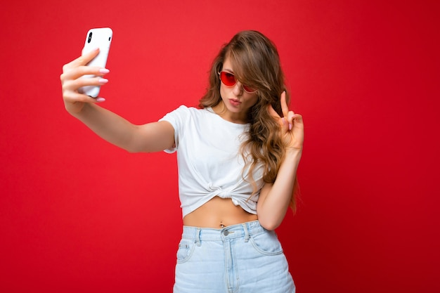 Photo of amazing beautiful young blonde woman holding mobile phone taking selfie photo using
