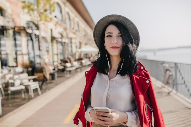 Photo of amazing black-haired woman with lovely face expression walking around city