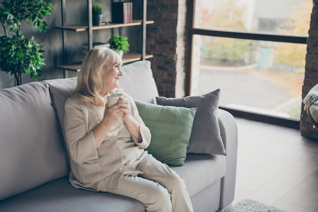 Photo of amazing blond adorable aged granny homey good mood drinking hot beverage looking dreamy to window memories sitting comfort sofa divan living room indoors