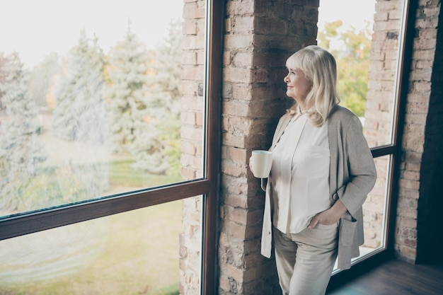Photo of amazing blond adorable aged granny homey good mood drinking hot beverage looking dreamy to window standing near brick wall flat indoors