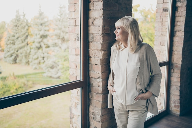 Photo of amazing blond adorable aged granny homey good mood looking dreamy to window standing near brick wall wear pastel beige pants shirt jacket flat indoors