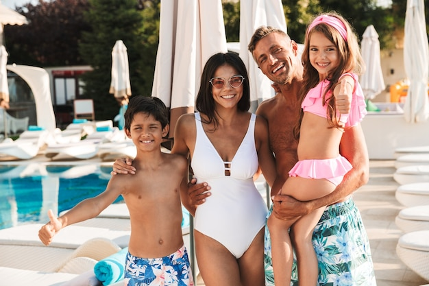 Photo of amazing caucasian family with children resting near luxury swimming pool, with white fashion deckchairs and umbrellas outdoor during recreation