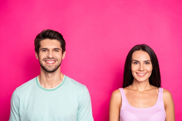 Photo of amazing couple guy and lady revealing perfect white teeth standing side by side wear casual clothes isolated vibrant pink color background