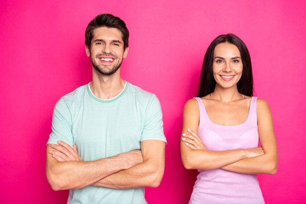 Photo of amazing couple guy and lady standing side by side with crossed arms reliable people wear casual clothes isolated vibrant pink color background