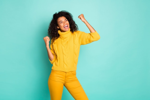 Photo of amazing dark skin lady holding hands raised celebrating lottery winning wear yellow knitted pullover stylish pants isolated blue teal color wall