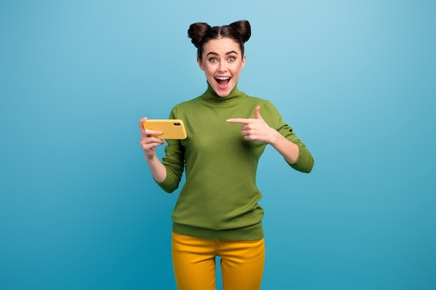 Photo of amazing lady hold telephone open mouth direct finger device advising cool wifi quality connection wear green turtleneck yellow pants isolated blue color wall