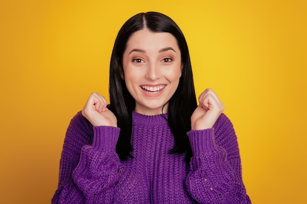 Photo of amazing lady win competition yelling raising fists celebrating wear sweater isolated yellow color background