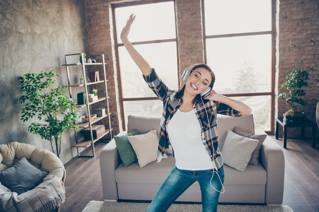 Photo of amazing pretty lady listening favorite melody in modern earflaps dancing overjoyed in light room near sofa wearing casual clothes apartment indoors