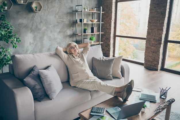 Photo of amazing white haired aged granny business lady having rest pause holding hands behind head carefree lazy mood dreamer legs on table sitting divan room office indoors